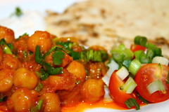 Chickpea curry served with nan and spring onion an…