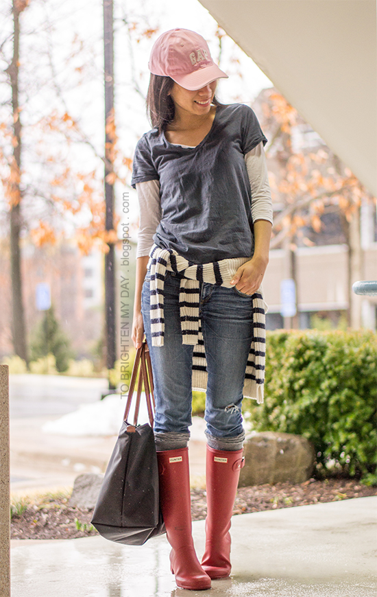 pink cap, navy tee, striped sweater, red rain boots