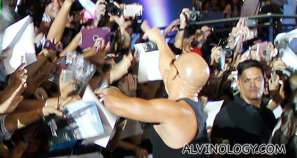 Greeting fans as he walks in
