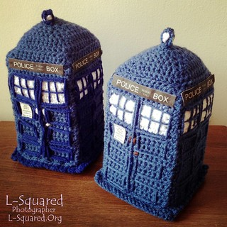 Two medium blue crocheted British Police Public Call Boxes, aka TARDISes.