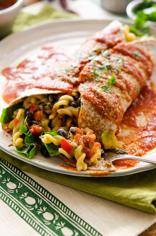 Large burrito on a plate, stuffed with Mac and cheese, and slathered in red sauce