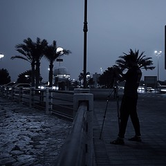 #photographer in the #night in #muharraq #bahrain #coast #highway #water #tripod #camera #trees #lights