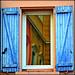 Reflet dans la fenêtre aux volets bleus