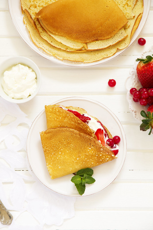 Pancakes filled with whipped cream and berries.