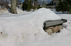 Stone wall emerges from melting snow