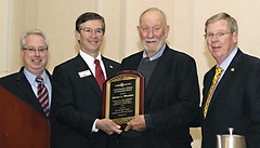 Jim Rhoden, second from right, accepts the Cobb County Lifetime Achievement Award from, from left, Georgia Attorney General Sam Olens, Cobb Chamber Chairman Greg Morgan and Sen. Johnny Isakson (R-Ga.) during the Cobb Chamber of Commerce First Monday Break
