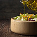 Olive oil pours from glass jug into a vegetable salad in a wooden dish by Karpenkov Denis