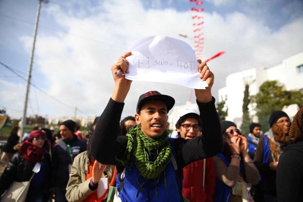 志工拿著寫著「4天=40第納爾(折合新台幣約640元)」的標語,在WSF場地中進行罷工。(攝影:陳逸婷)