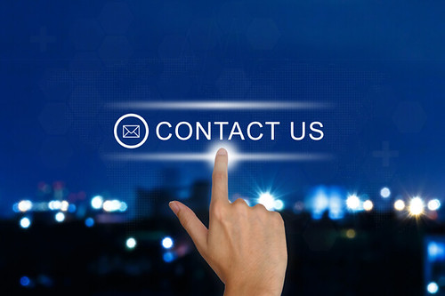 hand pushing contact us button on touch screen