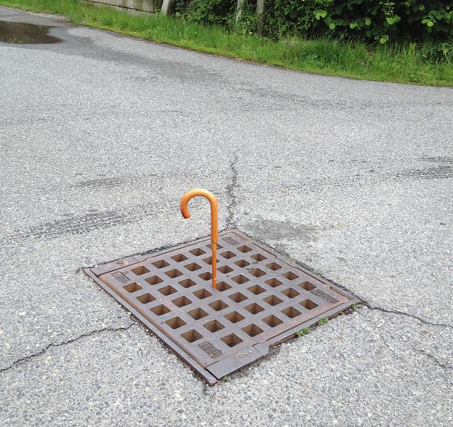 Regenschirm im Kanaldeckel