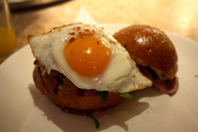 Chilli fried egg & bacon brioche roll, spiced mango chutney & rocket at Granger & Co., Notting Hill, London