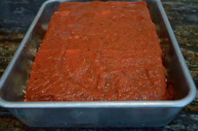 The marinara sauce after it has been spread evenly across the top.