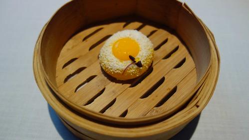 Bollo cocido relleno de rabo de toro con una yema de huevo de codorniz