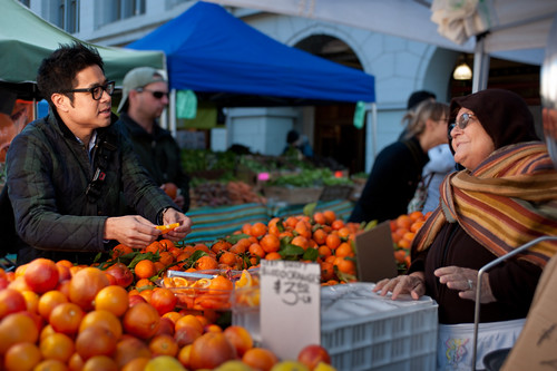 A farmer's market patron enjoys orange samples and talks to the booth vendor at a San Francisco area market. The new Farmers Market API released by AMS will give app developers and designers an easier way to leverage the wealth of information in USDA's National Farmers Market Directory. Photo by Gary Yost.