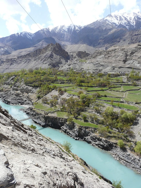 The Indus flows from left to right, with terraced fields and orchards on the far bank. The mountains loom over the fields