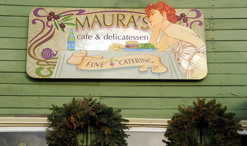 Maura's cafe & delicatessen, fine catering, red headed woman at a table, olives, snail, art nouveau sign, wreaths, old town, Homer, Alaska, USA by Wonderlane