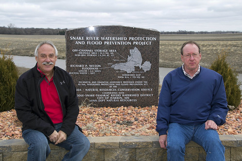 Doug Sorenson, Middle-Snake-Tamarac Rivers Watershed District board member, and Nick Drees, the district's Administrator, sitting by the Richard P. Nelson Floodway monument. (NRCS photo/ Julie MacSwain)