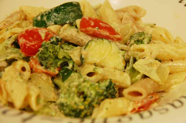 vegetables in creamy sauce on bed of pasta