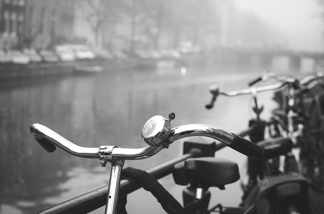 Bikes parked along one of Amsterdam's many canals on a foggy morning.