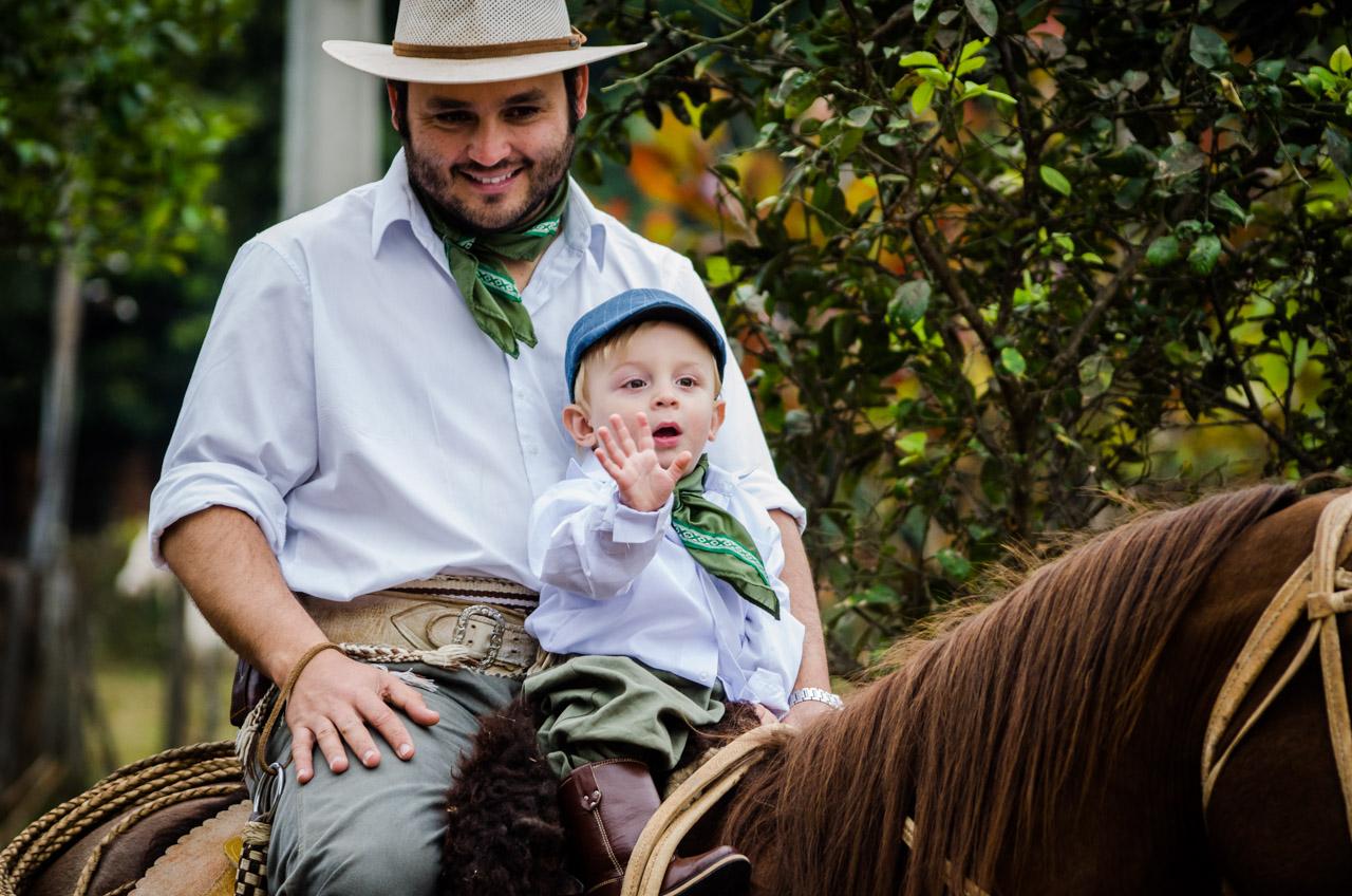 Un pequeño integrante de la Caballería Ñasaindy saluda al público durante el desfile en compañía de su padre en la tradicional ciudad de San Juan. El desfile de caballerías se realiza todos los años durante las fiestas de San Juan. (Elton Núñez)
