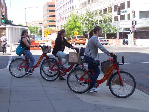 3 people riding Capital Bikeshare bikes on M Street NW, after shopping