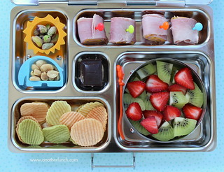Kindergarten school lunch - ham & cheese rolls, nuts, veggie chips, strawberries and kiwi, organic dark chocolate