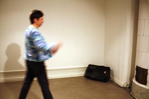 En besökare inne i rummet rör sig med och mot den svarta högtalaren i hörnet.