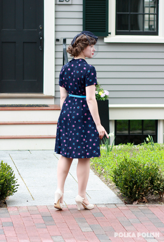 A 1940s daytime look with a navy polka dot dress, small tilt hat, and cream BAIT Footwear heels