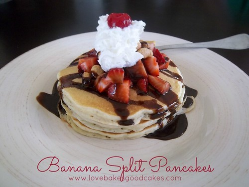 Banana Split Pancakes with chocolate syrup, strawberries, whipped cream and cherry stacked on plate