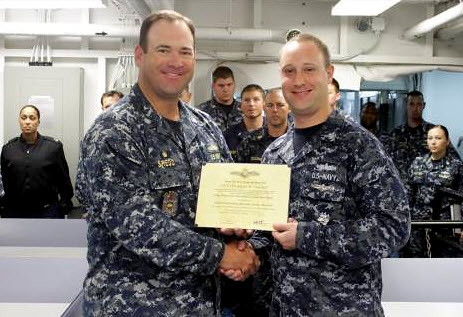 Adam Overton receives his Enlisted Information Dominance Warfare Specialist qualification from CO Commander Stephen Shedd