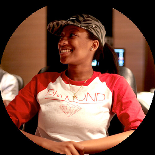 Wondagurl - a young black woman with a baseball cap and big smile - relaxes in a recording studio