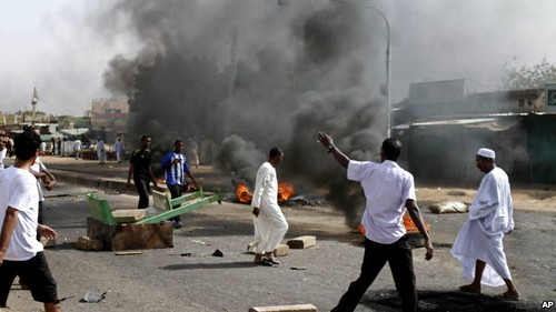 People walk around fires in Sudan where unrest over rising fuel prices has resulted in dozens of deaths. Some protesters are out for regime-change. by Pan-African News Wire File Photos