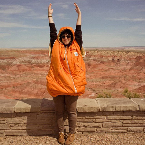 a woman wearing an orange Napsack, hands over her head