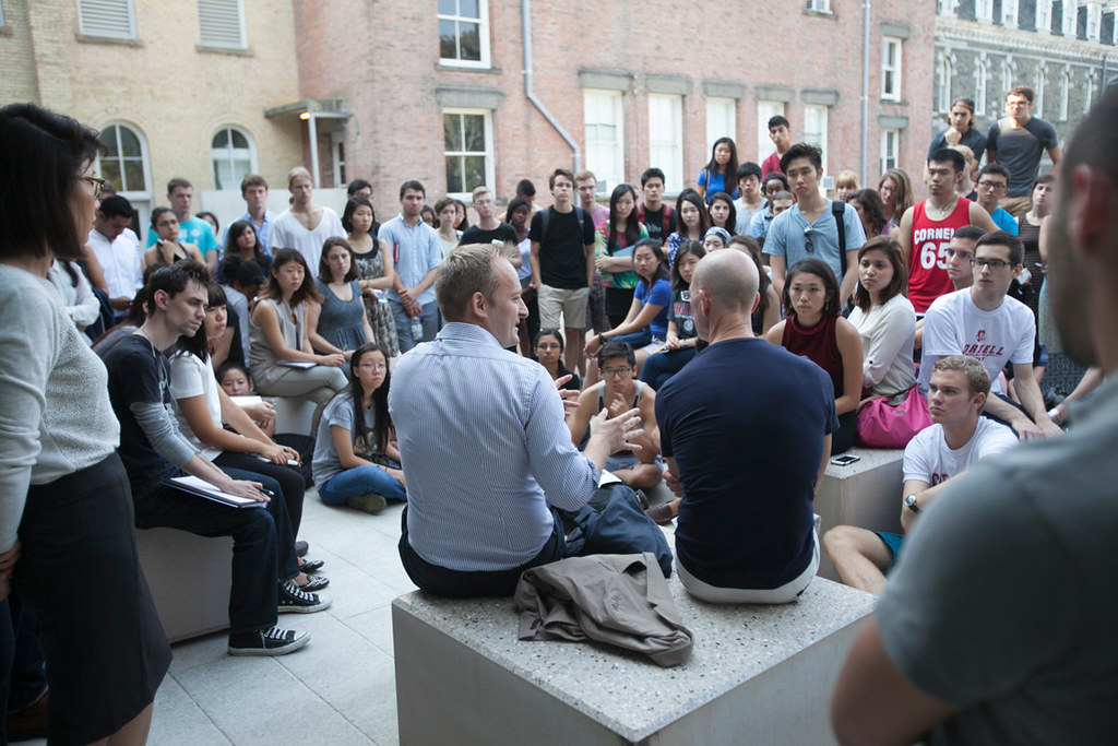 Vladimir Pajkic (B.Arch. '00), on left, sits with Herzog in conversation with students at the Milstein Hall West Plaza.