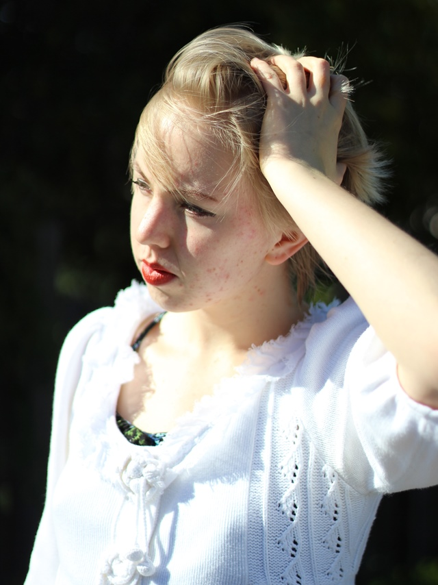 bright white cardigan, blonde pixie cut