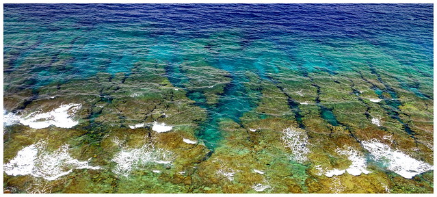CRACKS, CREVASSES, AND UNDER-SEA CANYONS DESCEND FROM THE SHALLOW REEFS ALONG THE NORTH SHORE of IE ISLAND