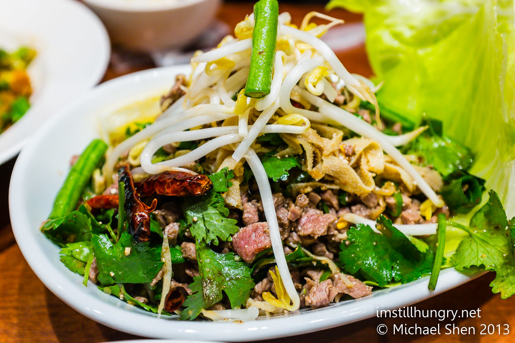 LARB (beef) - A warm cooked salad of ground minced meat tossed with lime juice, red onion, roasted rice and roasted chilli flakes, topped with mint leaves, shallots and coriander holy basil