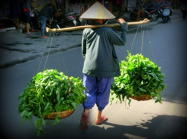 A woman carries a yoke basket down the streets in Hoi An, Vietnam