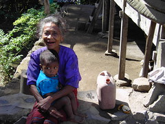A face of many seasons.Scrawny Flores lady and child in traditonal thatched village on island of Flores Indonesia.