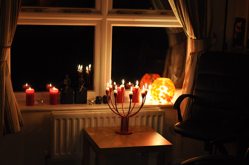 Diwali - image of windowsill and table with a red candelabra full of candles, and an orange lamp
