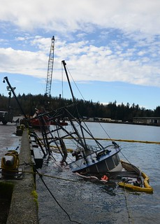 The Coast Guard Sector Columbia Incident Management Division works with Port of Astoria personnel to refloat and lift the vessel Cap'N Oscar, after it sunk at the Port of Astoria, Ore., Feb. 11, 2015. Providing coordinated and effective response to the release of pollution is one of IMD's main objectives and part of the Coast Guard's marine safety mission. (U.S. Coast Guard Photo taken by Petty Officer 3rd Class Jonathan Klingenberg)
