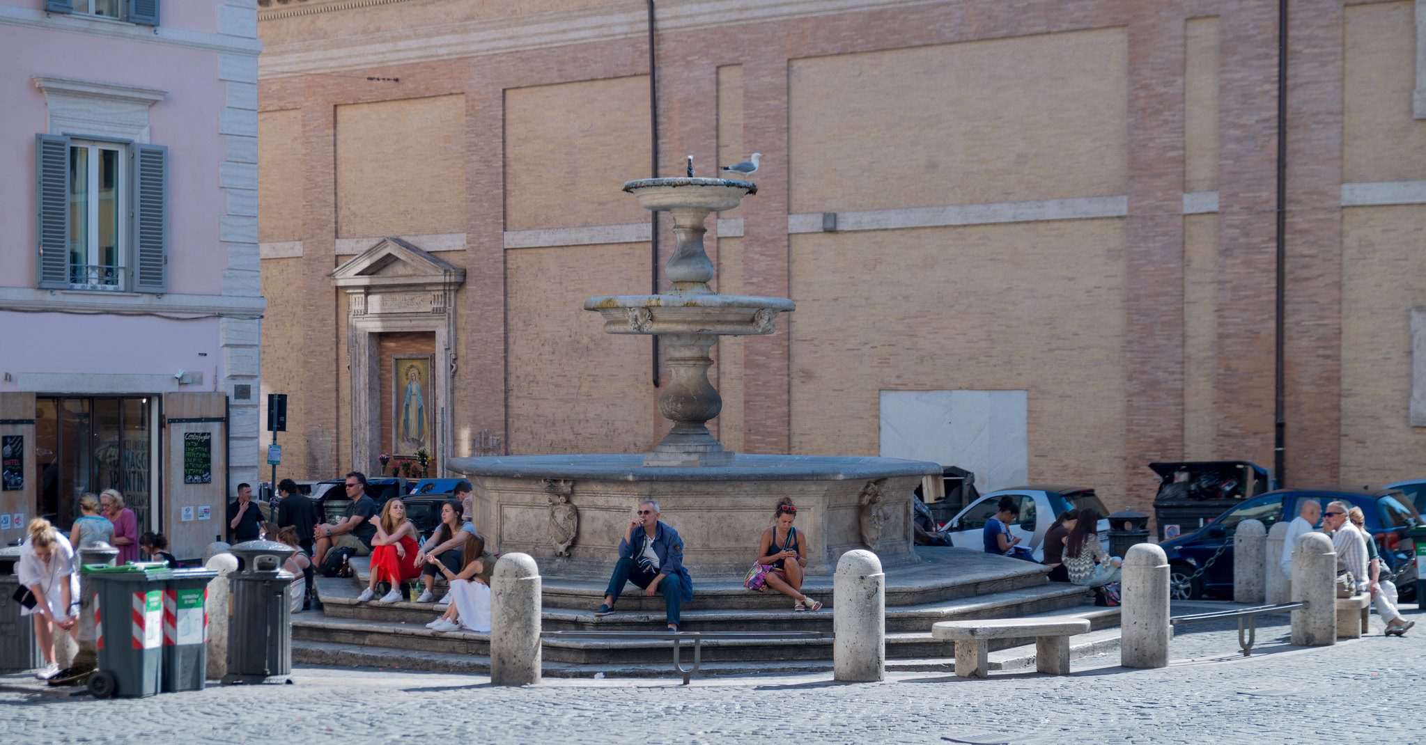 Street view of people sitting around a Roman fountain