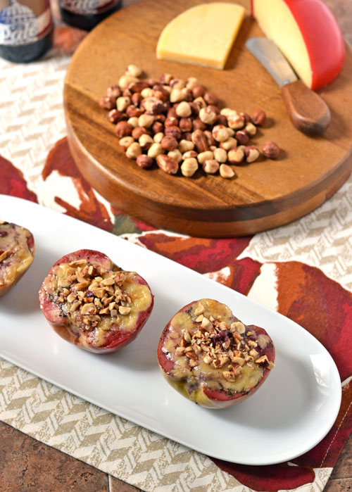 Baked apples with cheese and hazelnuts on a white plate