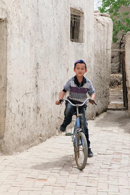 Doppa weared boy riding a bicycle, Kumul (Hami) ハミ、自転車に乗るドッパ少年