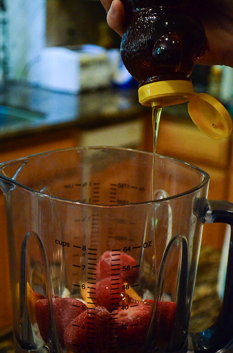 Honey is drizzled into the blender.