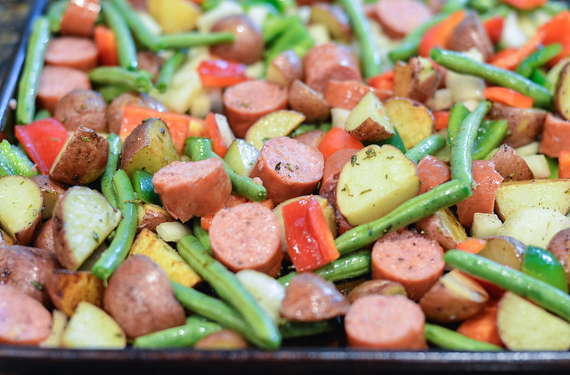 After tossing some sliced, smoked sausage, onion, bell pepper, and ...