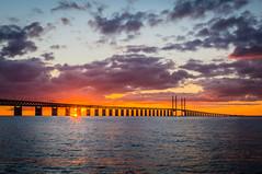 Sun flare by a dark silhouetted Øresund Bridge