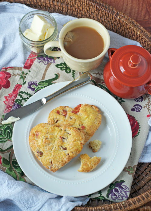 Two heart-shaped scones filled with strawberries on a white plate