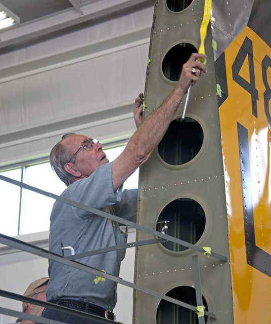 Photo of Champaign Aviation Museum volunteer with vertical tail of B-17 Champaign Lady