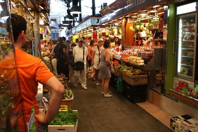 Commerçant dans une allée du marché de la Boqueria à Barcelone